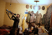 "UKRAINE, 02.2016, Novohrodivka, Oblast Donetsk. Ukrainian-Russian conflict concerning Eastern Ukraine / Foreign volunteers (""Task Force Pluto"") fighting with the far-right militia Pravyi Sektor against the Russian-backed separatists: Ben and Alex (Austria) cleaning guns and an RPG-7 launcher in their sleeping room at the base after returning from the frontline. © Timo Vogt/EST&OST"
