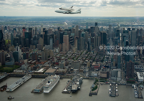 Space shuttle Enterprise, mounted atop a NASA 747 Shuttle Carrier Aircraft (SCA), is seen as it flies near the Intrepid Sea, Air and Space Museum, Friday, April 27, 2012, in New York. Enterprise was the first shuttle orbiter built for NASA performing test flights in the atmosphere and was incapable of spaceflight. Originally housed at the Smithsonian's Steven F. Udvar-Hazy Center, Enterprise will be demated from the SCA and placed on a barge that will eventually be moved by tugboat up the Hudson River to the Intrepid Sea, Air & Space Museum in June. .Mandatory Credit: Robert Markowitz / NASA via CNP