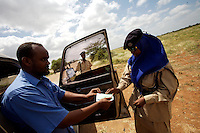 Awa Issac, 23 years old, Police officer in the TFG ( transitional Federal Government ) police force controls the documents of a driver at the Baidoa Airport in Somalia on Wednesday January 03 2007..Only a few days after the fall of the United Islamic Courts in Mogadishu, Ethiopian and Transitional Federal Government troops are patrolling the city and securing strategic locations..The people in Mogadishu appear confused and doubtful on t