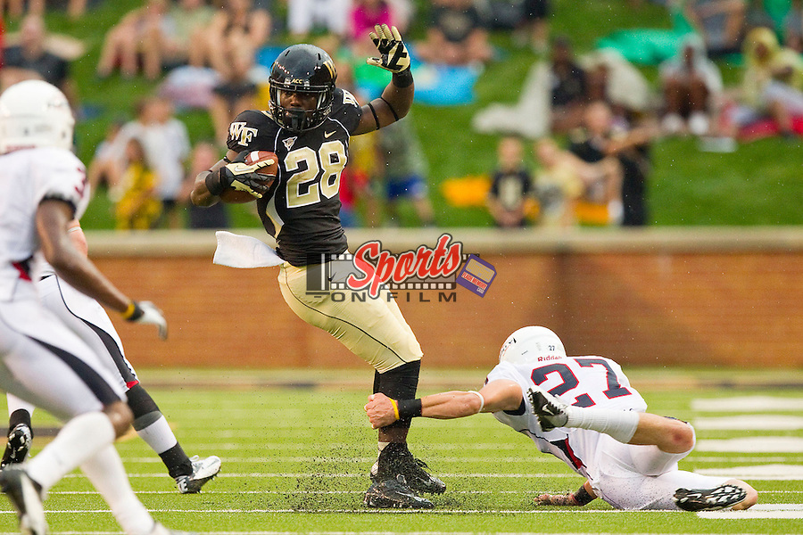 Deandre Martin (28) of the Wake Forest Demon Deacons tries to avoid being tackled by Jacob Hagen (27) of the Liberty Flames at BB&T Field on September 1, 2012 in Winston-Salem, North Carolina.  The Demon Deacons defeated the Flames 20-17.  (Brian Westerholt/Sports On Film)