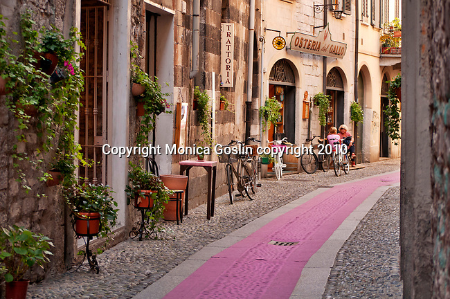 Street scene in Como, Italy a city on Lake Como where a pink carpet stretches down a cobble stone street