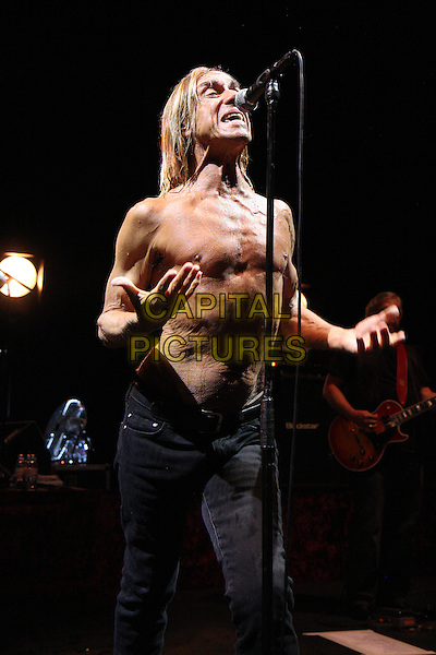IGGY AND THE STOOGES (Iggy Pop (born James Newell Osterberg)).Performing live at the Hammersmith Apollo, London, England..May 2nd, 2010.stage concert live gig performance music half singing hands length black jeans denim chest wrinkled skin full 3/4 funny .CAP/MAR.© Martin Harris/Capital Pictures.