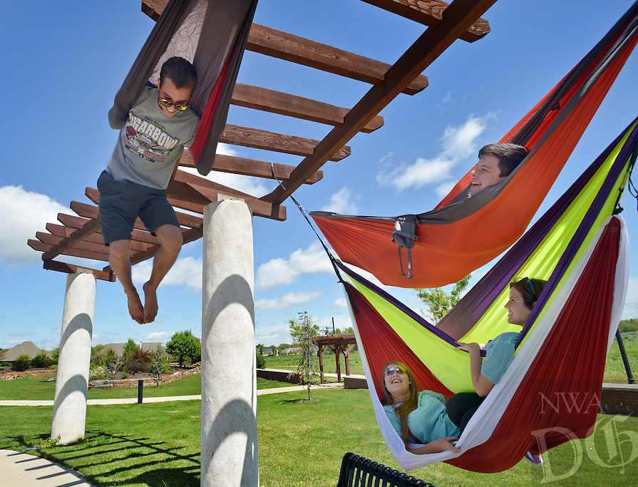 NWA Democrat-Gazette/BEN GOFF -- 04/19/15 Austin Howard (clockwise from left), 16, mounts his hammock with a bit of acrobatics as his friends from Bentonville High School Shay Longmate, 17, Tatum Palmer, 17, and Brett McConnell, 16, look on while hanging out at Orchards Park in Bentonville on Sunday Apr. 19, 2015.
