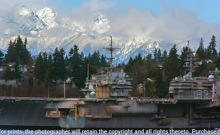 Snow covered Olympic mountains in Washington's Olympic National Park dwarf the aircraft USS Kitty Hawk (CV 63) and the USS Ranger (CV 61) mothballed at the Naval Base Kitsap in Bremerton, Washington. The Olympic Mountains is a year-round destination. In summer, visitors come for views of the Olympic Mountains, as well as for superb hiking. The weather in the Olympic Mountains is unpredictable, and visitors should be prepared for snow at any time of year. Jim Bryant Photo. ©2014. All Rights Reserved.