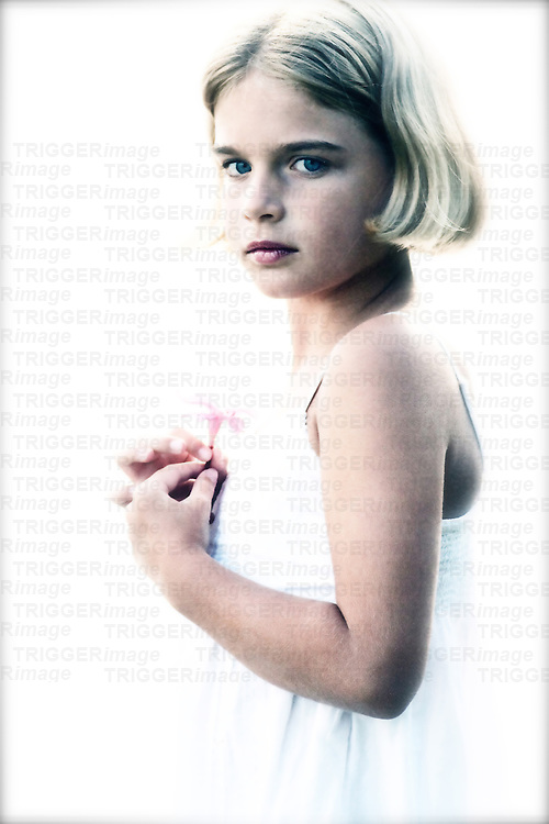 A young girl wearing a white summer dress holding a small flower