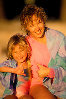 Mother and daughter giving shaka sign at the beach