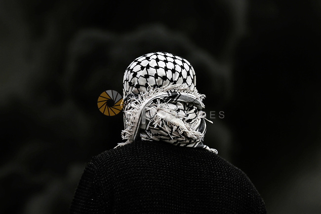 A Palestinian protester stands during clashes with Israel security forces following a weekly demonstration against the expropriation of Palestinian land by Israel in the village of Kfar Qaddum, near the West Bank city of Nablus on December 13, 2019. Photo by Shadi Jarar'ah