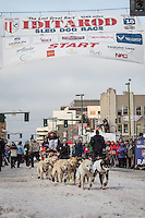 Marcelle Fressineau and team leave the ceremonial start line with an Iditarider at 4th Avenue and D street in downtown Anchorage, Alaska during the 2015 Iditarod race. Photo by Jim Kohl/IditarodPhotos.com