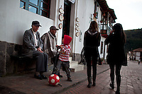 Dec. 21, 2011 - Mogui, Colombia. A little boy puts air in his football. © Nicolas Axelrod / Ruom