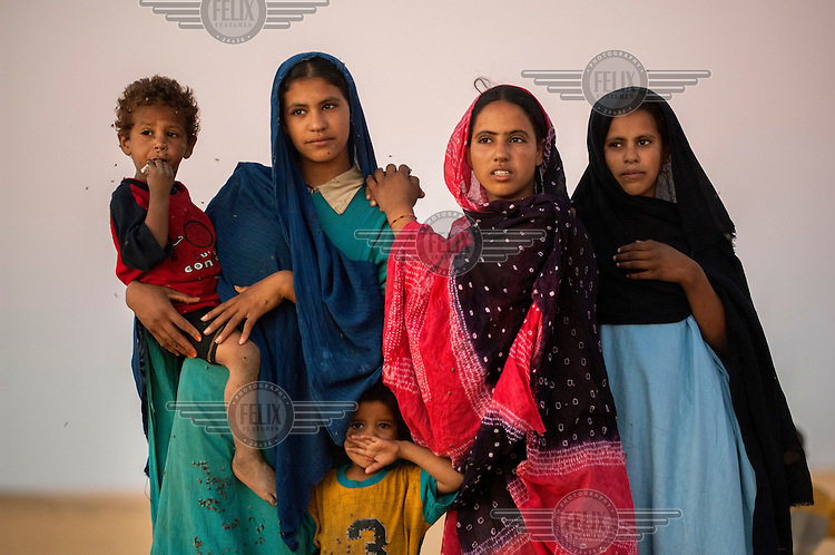 A portrait of an Arab Moor family, with a swarm of flies on and around them in the Sahara Desert town of Boujbeja. /Felix Features