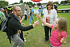 Dad handing a spinning plate to his daughter at a circus skills workshop at a Parklife summer activities event,