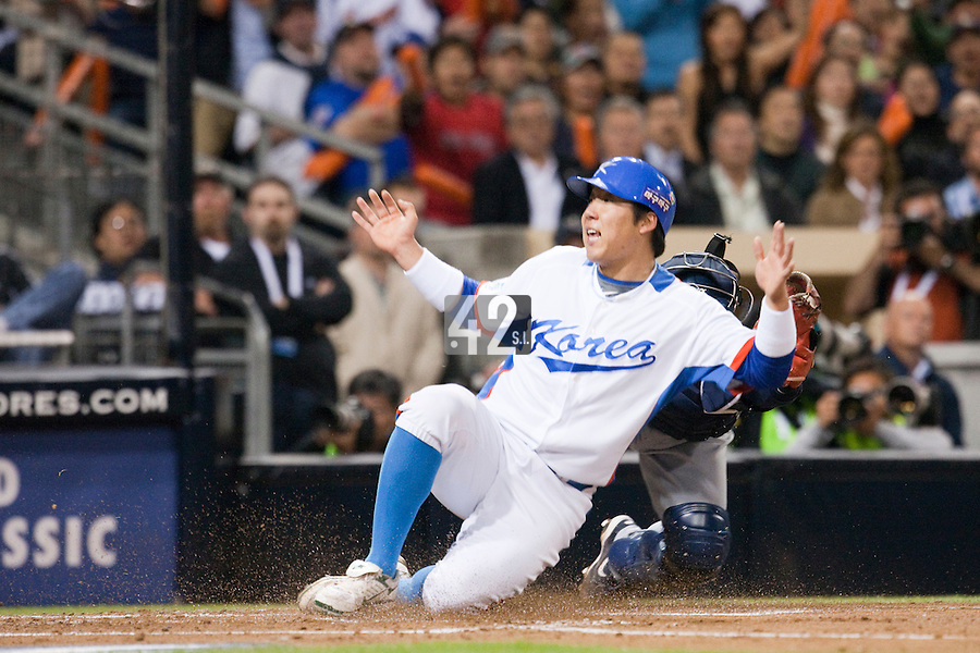 17 March 2009: #50 Hyun Soo Kim of Korea slides safely into home plate against #2Kenji Johjima of Japan during the 2009 World Baseball Classic Pool 1 game 4 at Petco Park in San Diego, California, USA. Korea wins 4-1 over Japan.