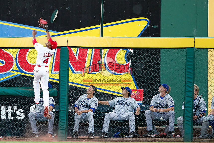 Daryl Jones (4) of the Springfield Cardinals leaps over the wall for a hard hit ball during a game against the Tulsa Drillers at Hammons Field on July 18, 2011 in Springfield, Missouri. Tulsa defeated Springfield 13-8. (David Welker / Four Seam Images)
