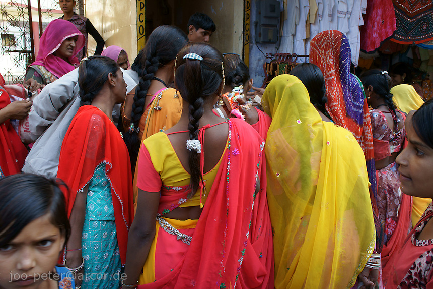 woman gather at street seller shop  while camel fair in holy city Pushkar while sunset time