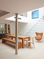 Contemporary wooden furniture is juxtaposed against a glass staircase in this kitchen dining area