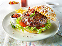 Char grilled beef burger  and bacon with chips and salad and a seseme bun photos. Funky Stock Photos