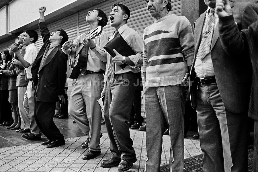Catholic street preachers, experiencing a religious trance, sing and play guitar on the street of Santiago de Chile, Chile, 2 March 2002.