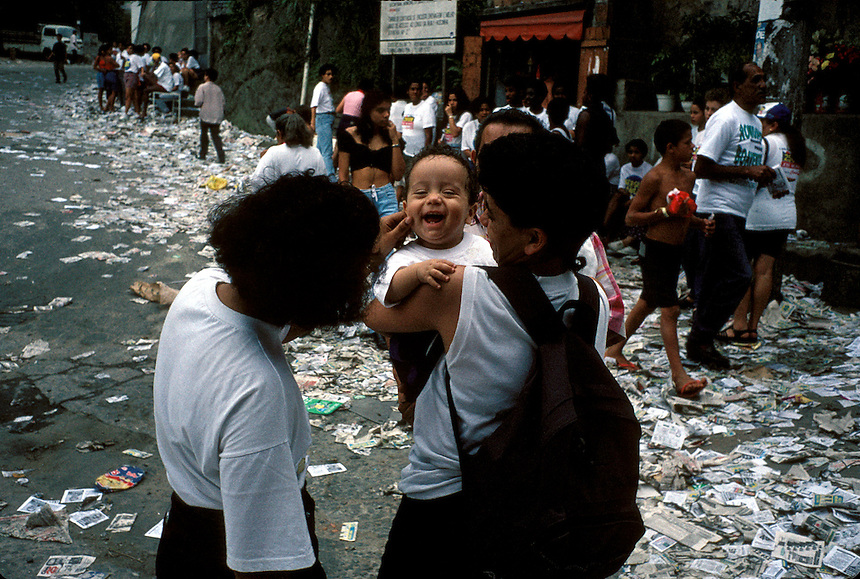 A baby is greeted with a pinch on the cheek in Rio's Rocinha slum on election day in October, 1996. Volunteers for candidates and parties pass out millions of promotional fliers — most of which are thrown on the ground — to people required by law to vote.