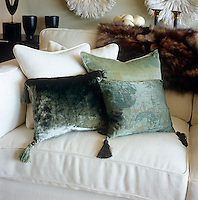 Sea-green tasseled silk cushions are contrasted against heavy cream linen in the living room of an apartment in London