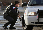 pvc010411c/1-4-11/asec.  APD Officer Wayne McCumber (CQ) crouches with a rifle behind his patrol car parked on the South side of UNMH on Lomas, as an active shooter situation unfolds, photographed Tuesday Jan. 4, 2011.  (Pat Vasquez-Cunningham/Journal)
