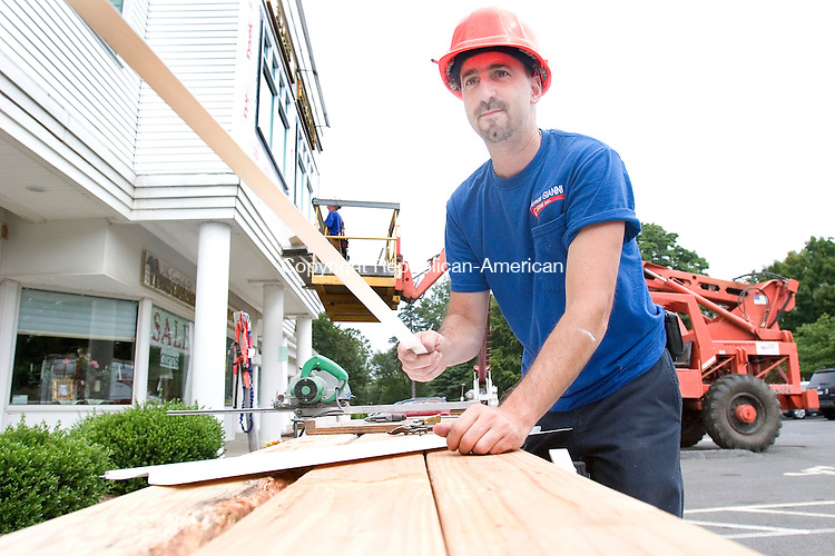 SOUTHBURY CT. 02 July 2010-080210SV05--Carmen Gianni cuts siding while his company puts in new windows and resides Dr. Steven Stirbl's offices at Playhouse Corner on Main Street South in Southbury Monday.<br /> Steven Valenti Republican-American
