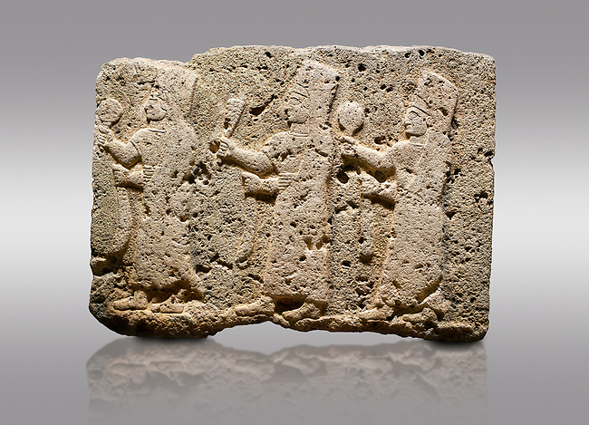 Picture & image of Hittite monumental relief sculpted orthostat stone panel of a Procession Limestone, Karkamıs, (Kargamıs), Carchemish (Karkemish), 900-700 B.C. Anatolian Civilisations Museum, Ankara, Turkey.<br /> <br /> It is a depiction of three marching female figures in long dress with a high headdress at their head. These women are considered to be the nuns of the Goddess Kubaba. The figures in the front and behind have a round mirror in their right hand while the figure in the middle has a bunch of spica in her right hand. Figures carry objects similar to a sceptre in their left hand.  <br /> <br /> Against a gray background.