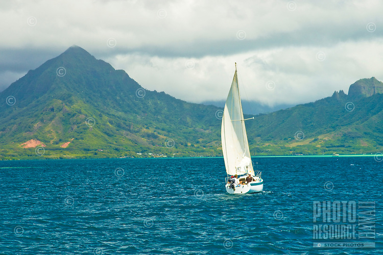 Sailboat cruises Kaneohe Bay with Kualoa Range in distance