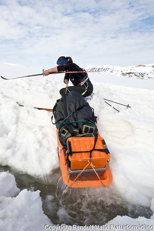 Dame krysser smeltevannselv nedenfor Sveabreen på Svalbard. ---- Woman crossing melt water stream on Svalbard.