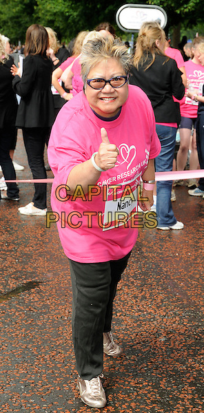 NANCY LAM.Cancer Research Race For Life Charity 5k Run at Hyde Park, London, England. .July 19th 2009 .full length pink t-shirt black jeans denim glasses bending leaning hand thumb up .CAP/CAN.©Can Nguyen/Capital Pictures.