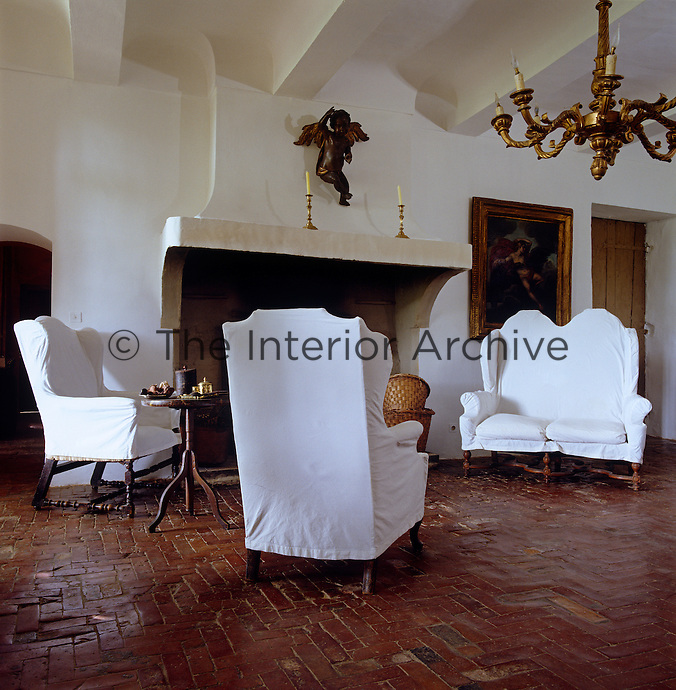 The chairs surrounding the huge fireplace are covered with white loose covers
