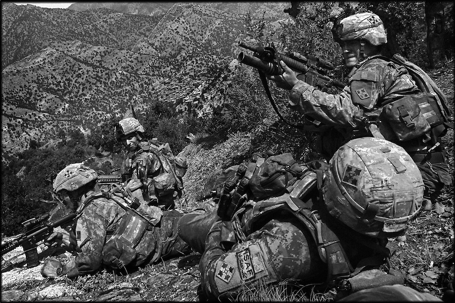 Soldiers from Baker Co. 2-12 Infantry Regiment 4th Brigade 4th Infantry Division fire on Taliban fighters at the end of a patrol on the slopes of Afghanistan's Korengal Valley in the summer of 2009.