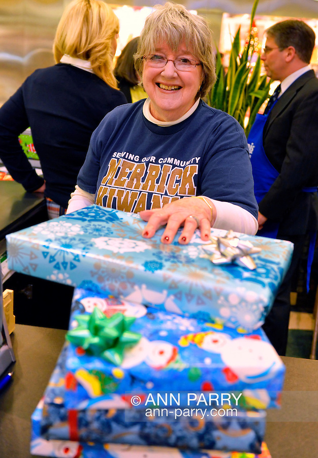 Dec. 12, 2012 - Garden City, New York, U.S. - SUE DILLON, a member of the Merrick Kiwanis Club, a community service group, gift wraps presents at Roosevelt Field mall on Long Island to help raise funds to use for charity, during the busy winter holiday shopping season. Some ways Kiwanis helps the community are by providing food, clothing, and school supplies to those in need, sending children to Kamp Kiwanis, providing scholarships and hosting a Harvest Ball for senior citizens.