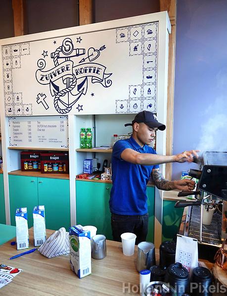 Nederland Zaandam 18 april 2018.  Barista aan het werk in koffiezaak Zuivere Koffie bij het station in Zaandam. Stichting Zuivere Koffie biedt gemotiveerde ex-gedetineerden kansen door het leren van een echt ambacht en relevante werkervaring. De werknemers krijgen een eerlijke kans op een succesvolle terugkeer in de samenleving. Zuivere Koffie wordt zowel binnen als buiten de gevangenis gebrand en verpakt. De koffie is biologisch en voorzien van het fairtrade keurmerk.  Foto mag niet in negatieve context gepubliceerd worden.  Foto Berlinda van Dam / Hollandse Hoogte