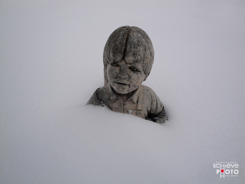 Statue of small boy in snow.
