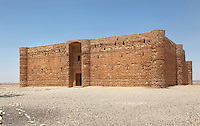 Qasr Kharana, desert castle, Jordan. This building was built c. 710 in the early Umayyad period under the Caliph Walid I although its purpose is unknown. It did not have a military function. It is a square building with small projecting corner turrets and a projecting round entrance seen here on the South side. It has 60 rooms inside over two floors around a central courtyard where rain is collected. The small slit windows are for light and ventilation. It fell out of use and was damaged by several earthquakes before being rediscovered in 1901 and restored in the 1970s. Picture by Manuel Cohen