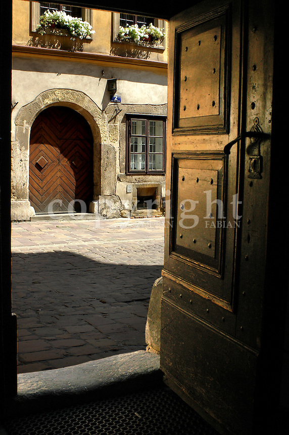 View of the street through an open wooden door from an old house in the old town of Cracow, Poland, Europe