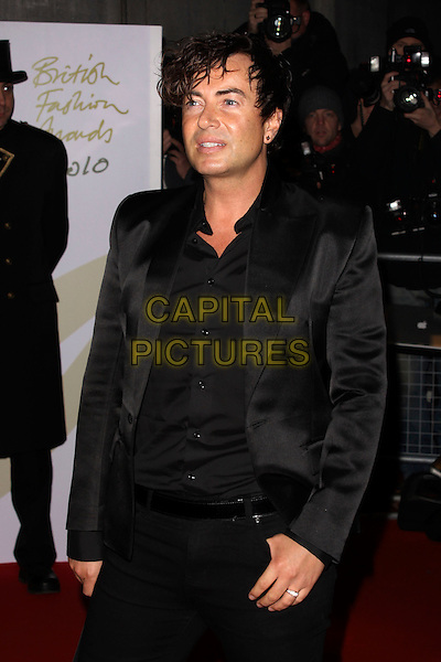 JULIEN MACDONALD.Attending the British Fashion Awards 2010, The Savoy Theatre, London, England..7th December 2010.half length black suit hand in pocket shirt .CAP/AH.©Adam Houghton/Capital Pictures.