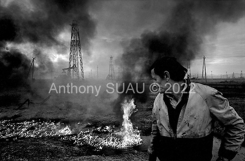 "Karbunara, Albania<br /> February 1997<br /> <br /> ""The Iron Forest"" is a vast landscape of oil drilling rigs across a flat plain. They function at the lowest capacity and pump only the lowest grade of oil. It is one of the few industries functioning in Albania today."