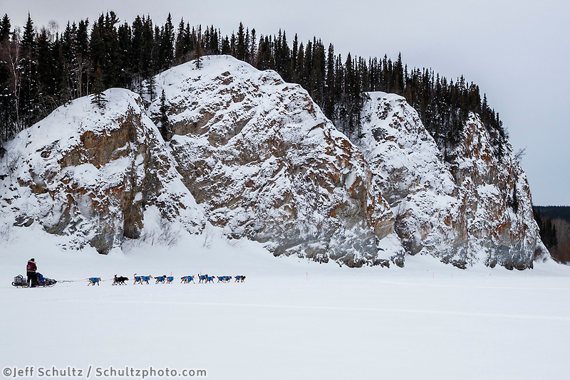 Noah Burmeister runs down the Yukon River past the cliffs of Ruby after leaving the Ruby checkpoint during the 2017 Iditarod on Thursday morning March 9, 2017.<br /> <br /> Photo by Jeff Schultz/SchultzPhoto.com  (C) 2017  ALL RIGHTS RESERVED
