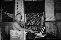 G-Land, Java, Indonesia.Photographer  Peter 'Joli' Wilson (AUS) working on his first laptop computer on the deck of his jungle accommodation  during the running of the 1996 Quiksilver G-Land Pro. The contest was won by Shane Beschen (HAW) with Gary Kong Elkerton (AUS) in second place..Photo: joliphotos.com