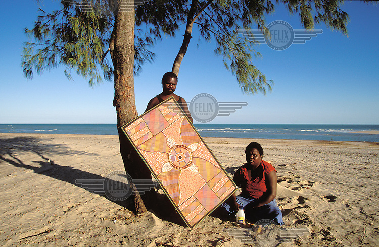 Tiwi Aboriginal artist Josie Orsto sits on the beach with her husband who holds one of her paintings about the sea.