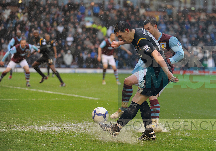 Gareth Barry of Manchester City gets in across despite the sodden pitch