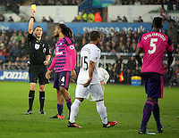 Papy Djilobodji of Sunderland (R) sees a yellow card by match referee Craig Pawson (L) during the Premier League match between Swansea City and Sunderland at The Liberty Stadium, Swansea, Wales, UK. Saturday 10 December 2016