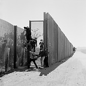 Naco, Arizona<br /> May 4, 2008<br /> <br /> West of Naco illegal immigrants scale the new 12 foot fence. Among them are women and a 10 year old boy. <br /> <br /> The vast majority of the Arizona/Mexican border is now marked by vehicle barrier or high fencing. Also a graded road runs along the majority of this new fencing.
