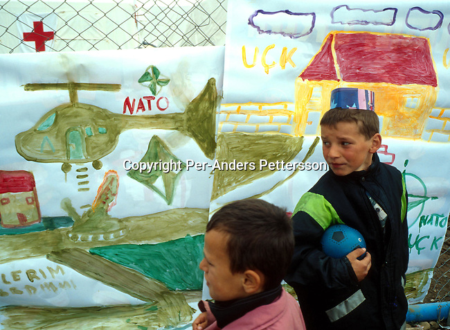 Ethnic Albanian refugee children from Kosovo watching drawings on May 16, 1999 in Stankovac, a refugee camp outside Skopje, Macedonia. The children was encouraged to draw pictures of their experiences as they fled with their families into Macedonia. Hundreds of thousands of people fled into Macedonia and Albania during the Serb terror of Kosovo..Photo: Per-Anders Pettersson/ iAfrika Photos
