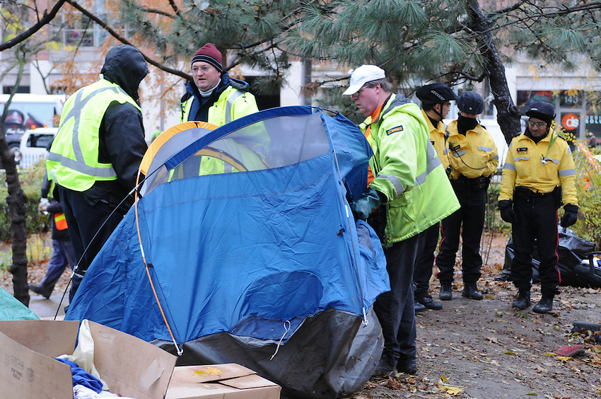 November 23, 2011, Toronto Police arrived in significant numbers this morning, beginning the process of evicting the Occupy Toronto tent camp from St. James Park.  Here Police stand watch as city workers dismantle and remove tents.