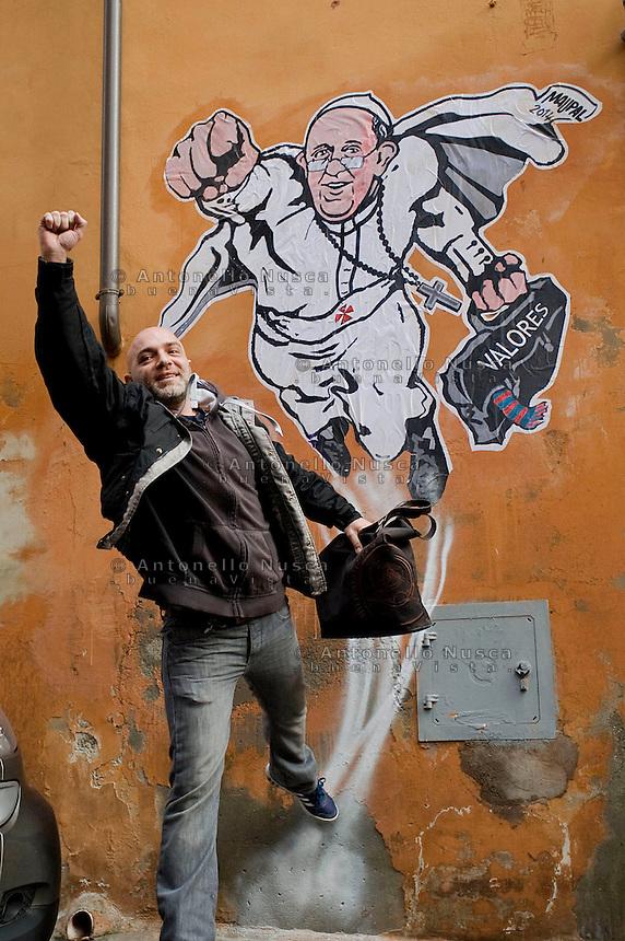 L'artista di strada Mauro Pallotta posa davanti la sua opera su di un muro a Borgo Pio, in cui ha raffigurato Papa Francesco come un supereroe proprio per rimarcare la mancanza oggi di un vero supereroe e il ruolo che il Pontefice pare stia ricoprendo. Street artist Mauro Pallotta poses in front of his graffiti featuring a 'superhero' version of Pope Francis in Borgo Pio, next to St. Peter's Square  in Rome. The image started circulating from the twitter account of the Vatican and has rapidly spread around the world.