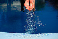 Feet of Australian woman tourist diving into swimming pool. Bali, Indonesia