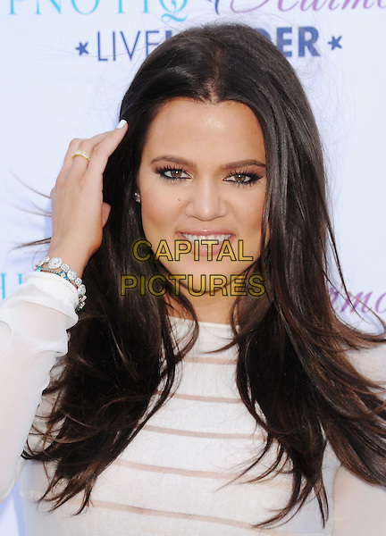 Khloe Kardashian Odom.Attends the launch of her custom cocktail recipe for HPNOTIQ Harmonie Liqueur at Mr. C Beverly Hills in Beverly Hills, California, USA..August 2nd, 2012.headshot portrait hand arm white cream sheer striped stripes top  .CAP/ROT/TM.©Tony Michaels/Roth Stock/Capital Pictures