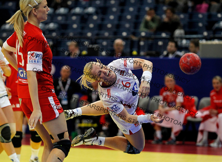 BELGRADE, SERBIA - DECEMBER 13:  Heidi Loke (R) of Norway scores the goal near Pernille Holst Larsen (L) of Denmark during the Women's European Handball Championship 2012 Group I main round match between Norway and Denmark at Arena Hall on December 13, 2012 in Belgrade, Serbia. (Photo by Srdjan Stevanovic/Getty Images)